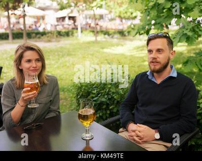 Les jeunes frère et sœur de boire une bière dans un café de la rue comme un concept d'amitié et de convivialité Banque D'Images