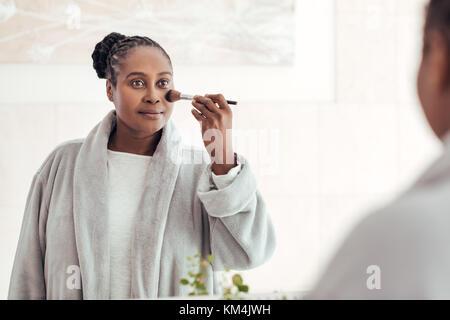 Femme africaine appliquant le maquillage de son visage dans une salle de bains Banque D'Images