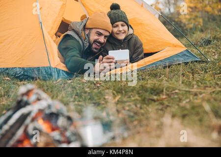 Père et fils en tenant avec smartphone selfies Banque D'Images