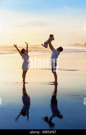 Père jetant en l'air en haut fils bébé, mère de sauter à l'eau extérieure. famille heureuse à pied avec plaisir Banque D'Images