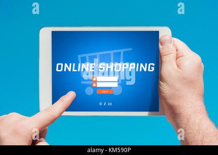 Man holding a tablet device visite un site d'achat en ligne et en touchant l'écran avec un doigt avec ciel bleu en arrière-plan.