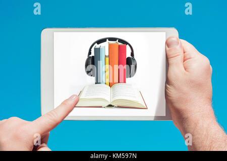 Homme tenant une tablette montrant des livres audio concept et de toucher l'écran avec un doigt avec ciel bleu en Banque D'Images