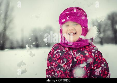 Enfant jouant avec des flocons de neige dans la forêt d'hiver Banque D'Images