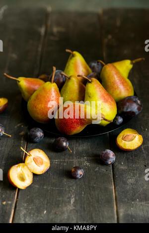 Studio shot les prunes et les poires sur platine alimentation saine Banque D'Images