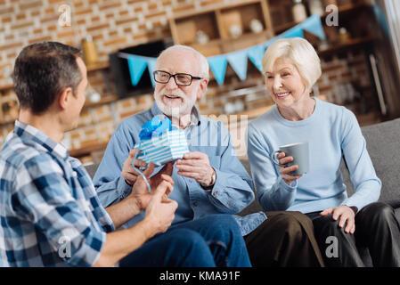 Fils aimant donner cadeau d'anniversaire à son vieux père Banque D'Images
