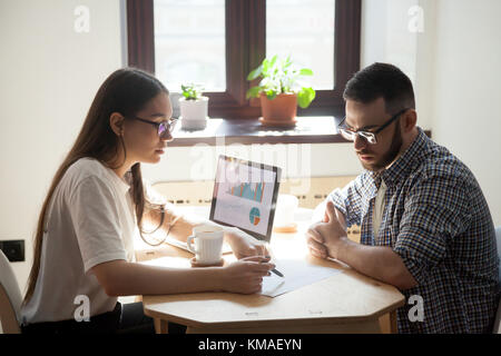 Deux collègues de travail millénaire discuter des problèmes sur d'affaires au bureau. smiling businessman un document Banque D'Images