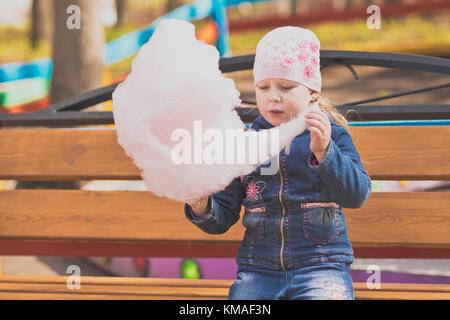 Petite fille sur un banc de parc eating cotton candy. portrait d'une jeune fille dans le parc sur une marche. Banque D'Images