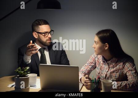 Mentor barbu à lunettes et costume expliquer jeune travailleuse des problèmes urgents de travail. travailler à échéance Banque D'Images