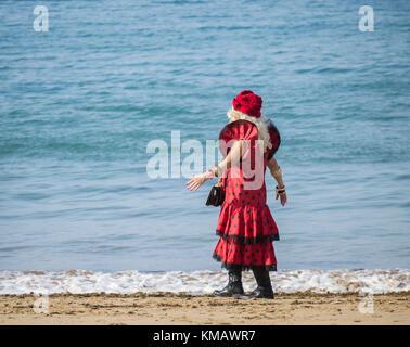 Femme âgée portant robe flamenco rouge à pois walking on beach en espagne Banque D'Images