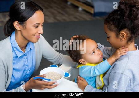 Mère et fille nourrir bébé Banque D'Images