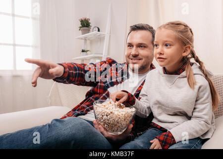 Père et fille eating popcorn Banque D'Images