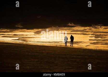Coucher du soleil - un couple vu en silhouette marcher le long de la ligne de rivage au cours d'une intense coucher Banque D'Images
