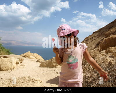 A smiling girl with lollipop on a hike