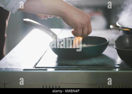Chef, c'est la cuisson de la viande et des légumes dans une casserole Banque D'Images
