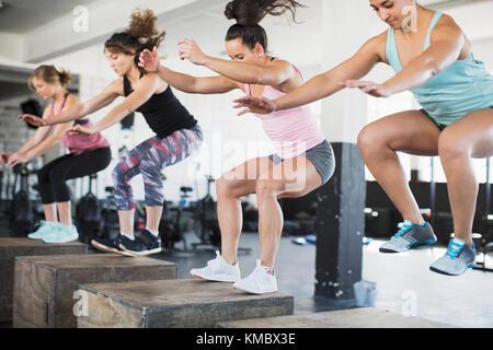 Femmes déterminées faisant sauter accroupi sur les cases de classe d'exercice Banque D'Images