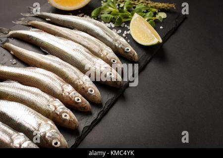 Poisson frais de la mer ou l'éperlan et prête pour la cuisson des sardines au citron, thym, gros sel de mer et sur Banque D'Images