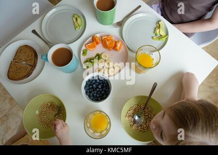 Mère et enfants de prendre le petit déjeuner Banque D'Images