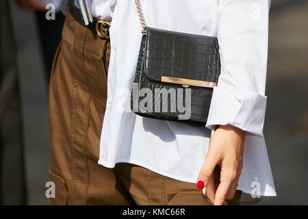 Milan - 23 septembre   femme avec veste en cuir crocodile noir, pantalon  brun et b757f2ce48f