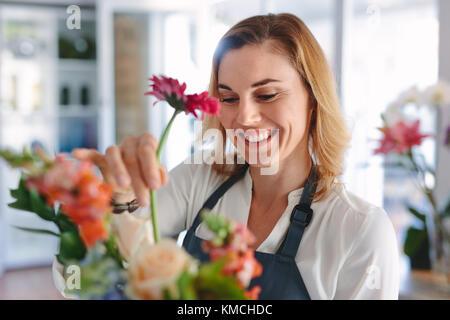 Female florist arranging flowers. Propriétaire d'une boutique de fleurs femme plaçant des fleurs dans un bouquet. Banque D'Images