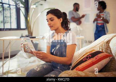 Jeune femme de boire du café et la visualisation d'échantillons de peinture dans la salle de séjour Banque D'Images