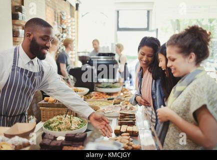 Travailleur homme aidant les clients de sexe féminin dans cafe Banque D'Images