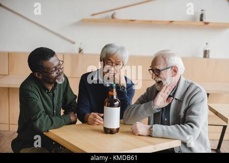 Les amis de bar avec une bouteille de bière Banque D'Images