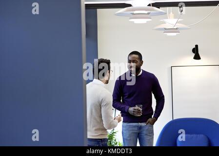 Le business informel dans un bureau contemporain, sourire et rire avec un collègue du Caucase durant une pause du Banque D'Images