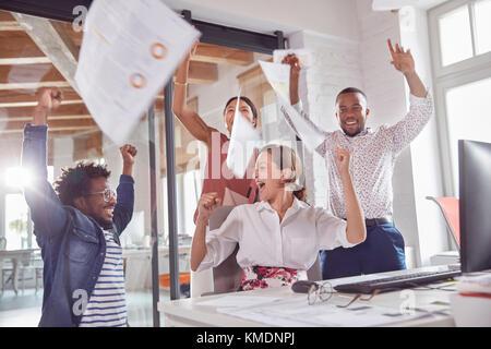 Les gens d'affaires exubérante célébration,jetant la paperasse dans office frais généraux Banque D'Images