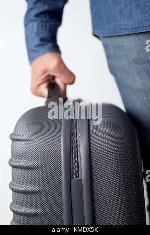 Libre d'un jeune homme de race blanche portant une valise par la poignée contre un fond blanc Banque D'Images