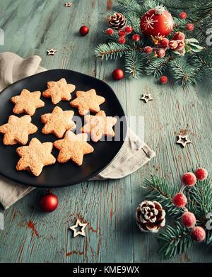 Fond de Noël rustique en vert et rouge en forme d'étoiles. Les cookies sur la plaque noire avec des décorations Banque D'Images