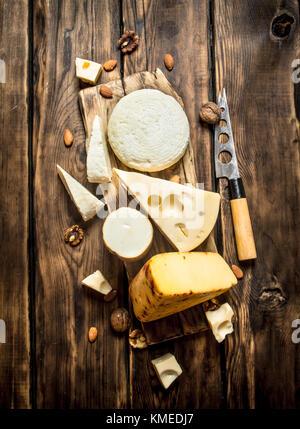 Morceaux de fromage avec les écrous à un conseil avec un couteau. sur une table en bois. Banque D'Images