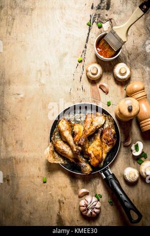 Cuisses de poulet frit à la poêle avec la sauce tomate, les champignons et l'ail. Banque D'Images
