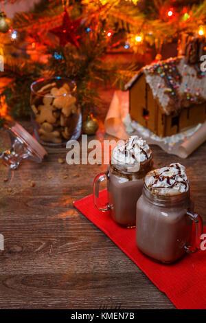Deux verres de cacao avec crème fouettée et sirop de chocolat sur la table de bois et d'épices maison, cookie jar Banque D'Images