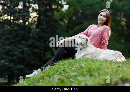 Photo de fille assise avec chien sur pelouse verte en été 24 Banque D'Images