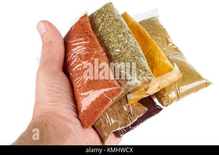 Variété d'épices turc en emballage transparent dans la main sur fond blanc: origan, Indes, cumin, chilly, d'épices Banque D'Images