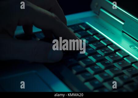 L'homme en appuyant sur une touche sur un clavier d'ordinateur portable Banque D'Images