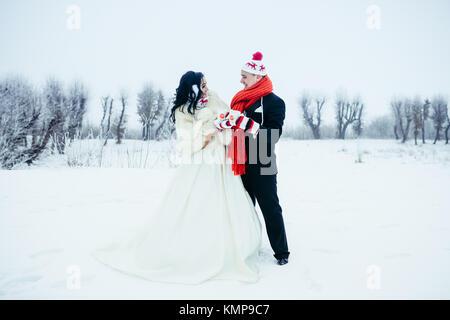 Long shot de la belle happy senior couple having fun on the Prairie enneigée. Ils portent des gants, bonnets et Banque D'Images