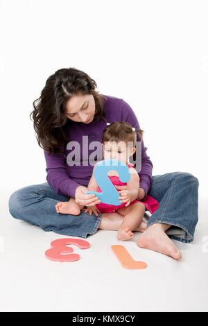 Mère, nounou, ou enseignant qui bébé à apprendre à compter un, deux, trois, avec les chiffres de manière ludique, Banque D'Images