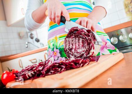 Woman's hands cutting chou rouge, derrière les légumes frais. Banque D'Images