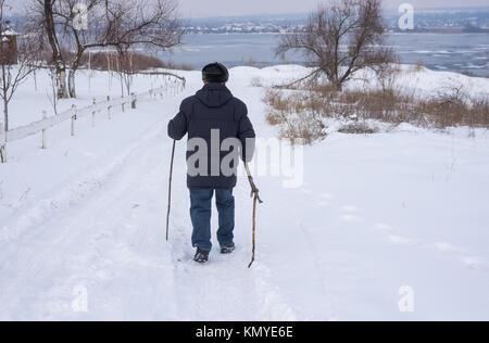 Man marche sur une route enneigée jusqu'au Dniepr congelé en Ukraine Banque D'Images