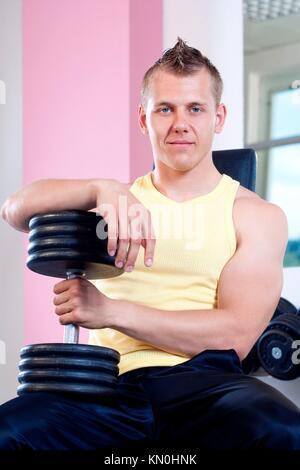 Portrait of a young man holding haltères en sport moderne Banque D'Images