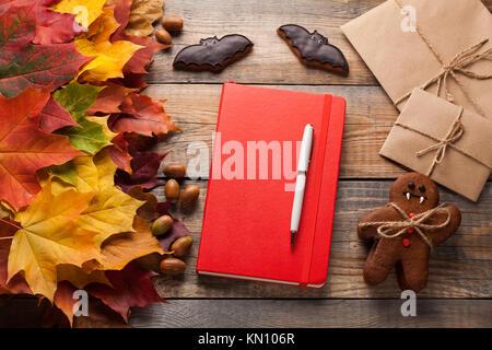 Cahier rouge et les cookies pour l'halloween sous forme de chauve-souris et des hommes de pain d'épice-vampires Banque D'Images