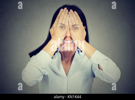Portrait of a smiling woman covering her eyes Banque D'Images