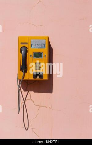 Téléphone rétro jaune sur le mur rose, Chine Banque D'Images