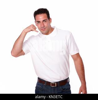 Portrait d'un charmeur sur t-shirt blanc avec permanent tout en geste de parler vous regarde sur studio isolé. Banque D'Images