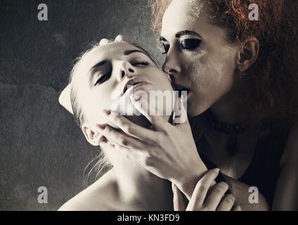 Vampire's kiss. Fantasy portrait féminin contre dark grungy origines. Banque D'Images
