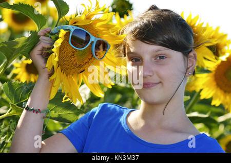 Belle jeune fille dans un champ de tournesol avec des lunettes. Banque D'Images