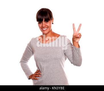 Young Girl holding up deux doigts en signe de victoire sur l'article robe gris sur fond blanc. Banque D'Images