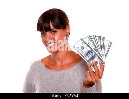Portrait of a smiling et jolie jeune femme tenant de dollars contre l'arrière-plan blanc.