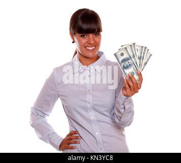 Portrait of a smiling pretty young woman holding dollars contre l'arrière-plan blanc.